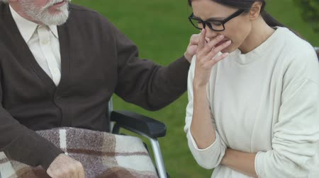 incurable : Daughter crying near old father in wheelchair, depressed with news about cancer Stock Footage