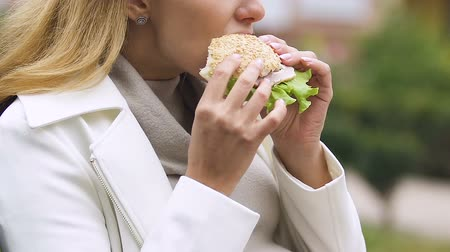 sensível : Young mother-to-be with big belly eating burger, suffering nausea, feeling sick