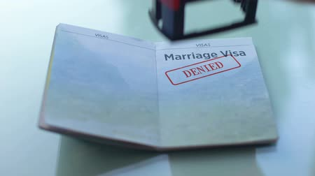 виза : Marriage visa denied, customs officer hand stamping seal in passport, travel