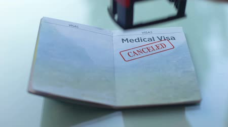 documents : Medical visa canceled, customs officer hand stamping seal in passport, travel Stock Footage