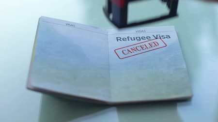 идентификация : Refugee visa canceled, customs officer hand stamping seal in passport, travel