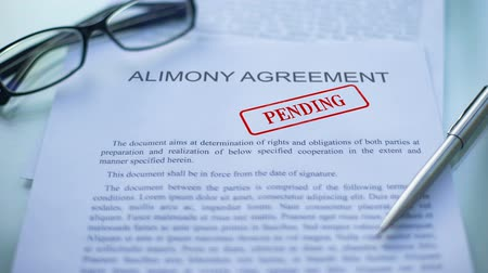 povinnost : Alimony agreement pending, officials hand stamping seal on business document