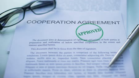 jóváhagyott : Cooperation agreement approved, officials hand stamping seal on document Stock mozgókép