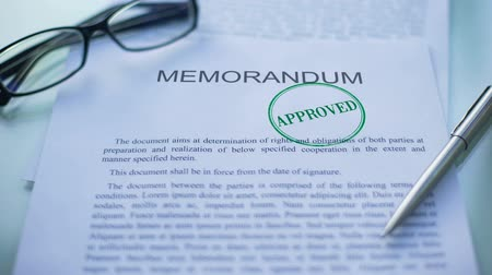 notaire : Memorandum approved, officials hand stamping seal on business document