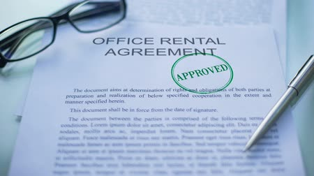legislação : Office rental agreement approved, hand stamping seal on business document, close