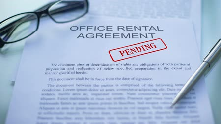 законодательство : Office rental agreement pending, hand stamping seal on business document, close