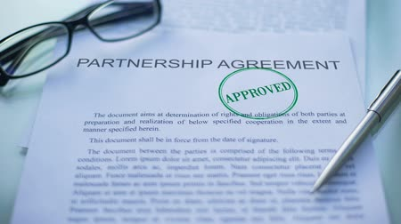 approved : Partnership agreement approved, hand stamping seal on business document, closeup