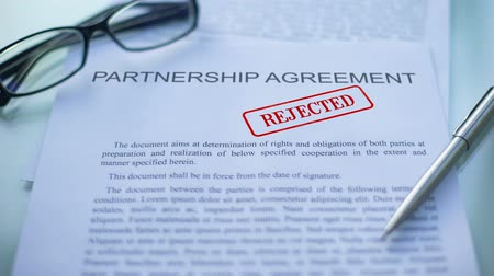 timbratura : Partnership agreement rejected, hand stamping seal on business document, closeup