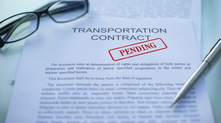 в ожидании : Transportation contract pending, hand stamping seal on business document, close