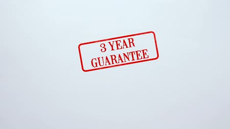 обещание : 3 Year Guarantee seal stamped on blank paper background, product quality Стоковые видеозаписи