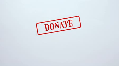 donate : Donate red seal stamped on blank paper background, charity project, kindness