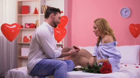duygusallık : Handsome man proposing to surprised girlfriend, giving ring and bunch of roses Stok Video