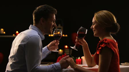 сладость : Sweet couple clinking glasses with red wine, date in high-quality restaurant