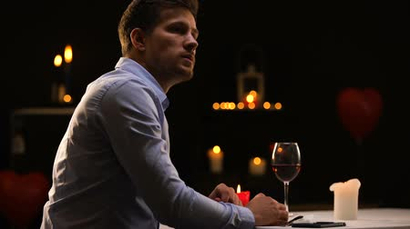 horeca : Unhappy man blowing out candles and leaving restaurant, unsuccessful date Stock Footage