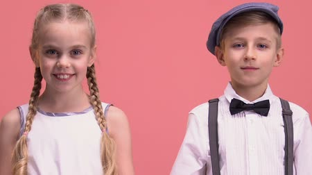 brothers : Cheerful little boy and girl looking into camera, isolated on pink background Stock Footage