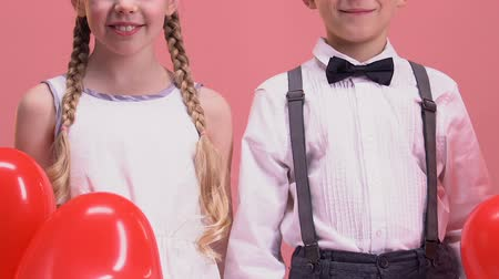 em forma de : Children with red balloons smiling to camera, taking photo on Valentines day Stock Footage