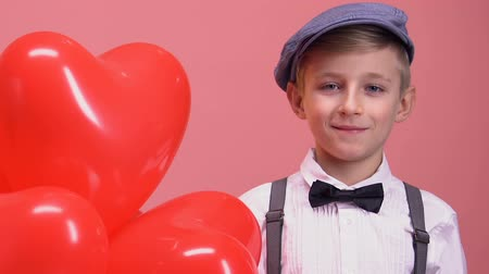 schoolkid : Shy little boy with heart-shaped balloons smiling to camera, Valentines day gift