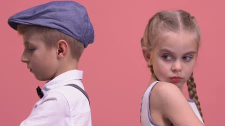 jealous : Offended kids couple standing back to each other, isolated on pink background