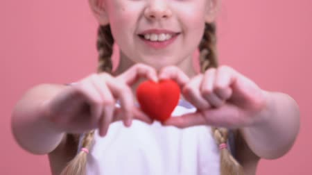 благотворительность : Little girl showing toy heart at camera closeup, charity and kindness concept