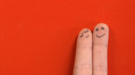art : Finger face couple in love isolated on red background, togetherness concept Wideo