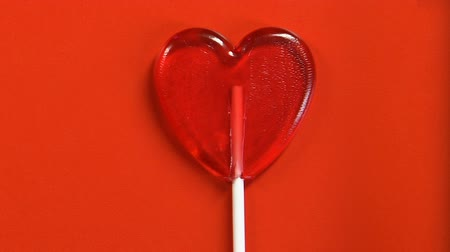 lolly : Heart-shaped lollipop isolated on red background, Valentines day symbol, topview