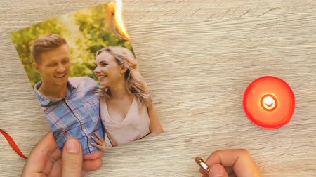ex boyfriend : Woman burning family photo and holding engagement ring, divorce and betrayal Stock Footage