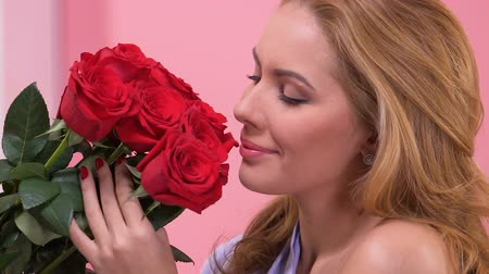 smelling : Beautiful woman admiring bouquet of red roses, surprise for Valentines day