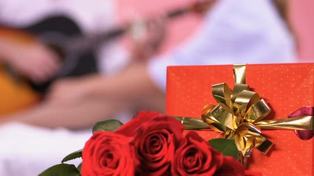 serenade : Gift and roses on bed, man playing guitar, singing romantic love song to woman