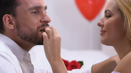 tentação : Woman seducing man with chocolates, kissing with love, romantic atmosphere