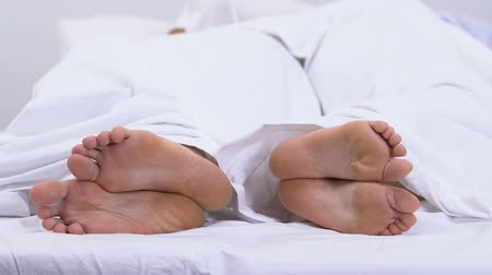 blote voeten : Feet of couple lying in bed under duvet, calluses and corns, fungal disease