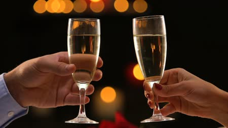 newyear : Couple celebrating New Year holding glasses with champagne, close-up hands