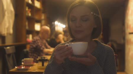 coffee house : Lady in her 40s spending evening in cafe and drinking soft flavored cappuccino