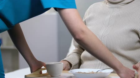 refusing : Naughty elderly female refusing to eat porridge in nursing home, untasty food