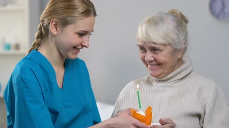 caregiver : Smiling medical worker bringing muffin with candle to happy senior woman, b-day