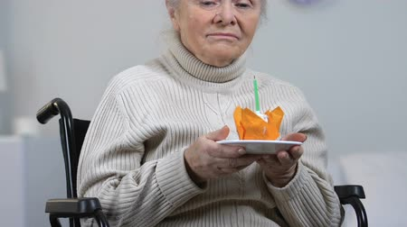 incurable : Depressed lonely woman in wheelchair blowing candle on cake and crying, misery