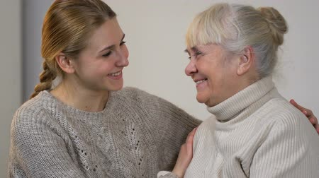 kötött : Granddaughter hugging happy smiling lady, friendly trustful relations in family