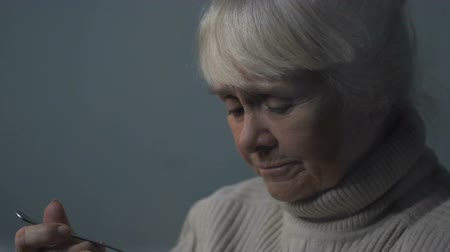 homesick : Upset senior woman eating tasteless porridge near rainy window in nursing home