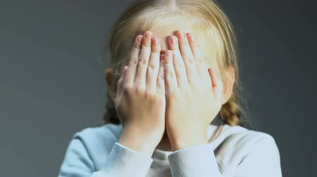witness : Little girl watching horror film, hiding face in hands, parental control service Stock Footage