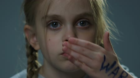 refugee crisis : Upset refugee child closing her eyes with palm, war inscription on hand, crisis
