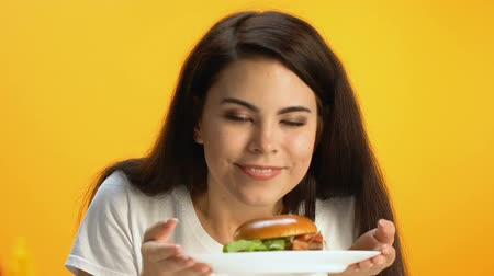 túlsúly : Beautiful brunette sniffing delicious burger and smiling, fast food, fatty meal Stock mozgókép