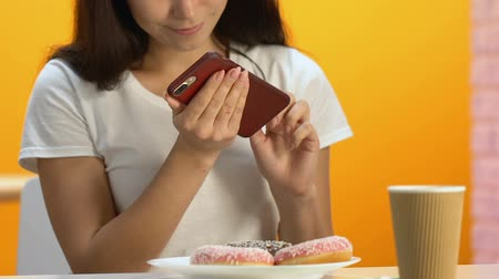 fotografando : Happy girl taking photo of appetizing doughnuts on cellphone, high calorie meal