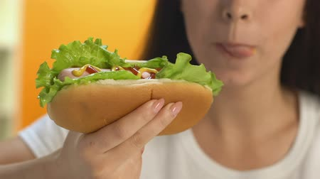 párek v rohlíku : Woman eating high calorie hot dog during lunchtime, fatty fast food snack, diet Dostupné videozáznamy