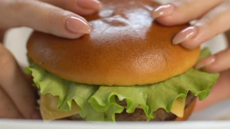 hambúrguer : Woman biting big fast food burger, gaining extra weight, saturated fat, closeup Vídeos