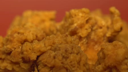 dobverő : Fatty crispy fried chicken on red background, unhealthy food concept, close up Stock mozgókép