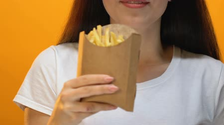 cheirando : Beautiful woman sniffing and proposing french fries in carton box, takeaway Stock Footage