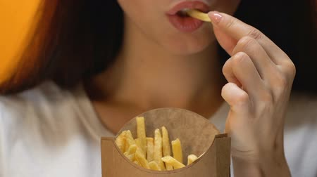 cheirando : Beautiful young woman eating fatty french fries, unhealthy fast food, close up