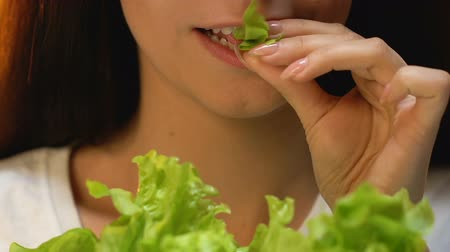 avoiding : Woman eating fresh lettuce and smiling, vegetarian diet, avoiding meat meals Stock Footage