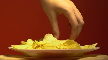 snoepen : Womans hand slowly taking one piece of chips, junk food addiction, close up