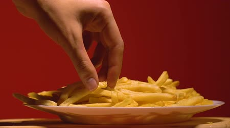 жарить : Woman slowly taking one piece of french fries, temptation on diet, nutrition
