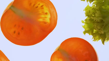 flat lay : Tomatoes and lettuce spinning on white background, vegetarian salad ingredients